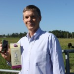 Dr. Tom Vickroy with smartphone in front of cow field.