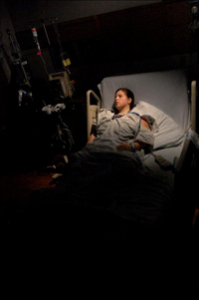 girl laying in a hospital bed surrounded by darkness with a light around her face